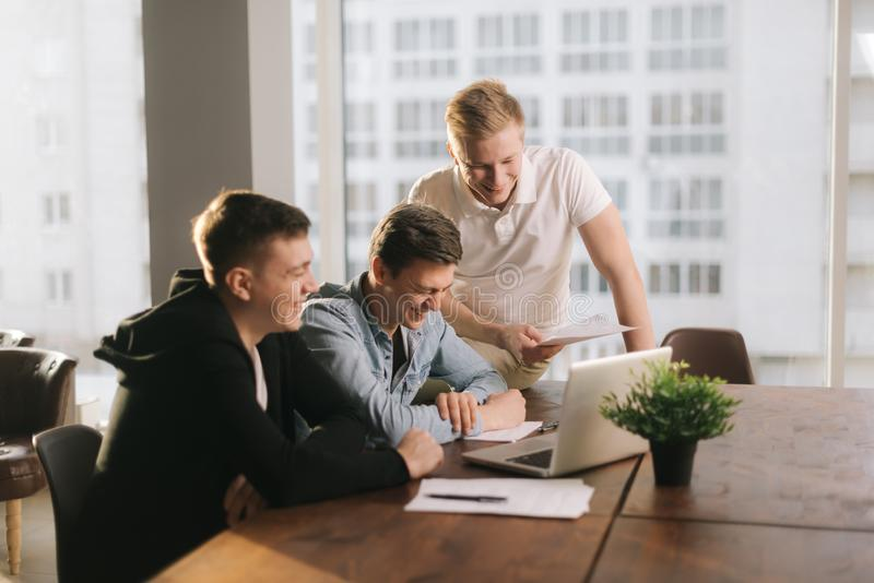 Business team young men having casual talk during meeting at the table stock image