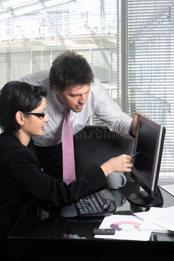 Business Teamwork. Young and good-looking business people are working tohether on a desktop computer in a modern office