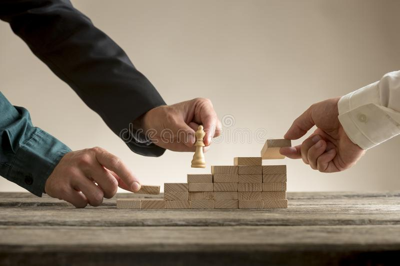 Business teamwork concept with a businessman moving a chess piece up a series of steps royalty free stock image