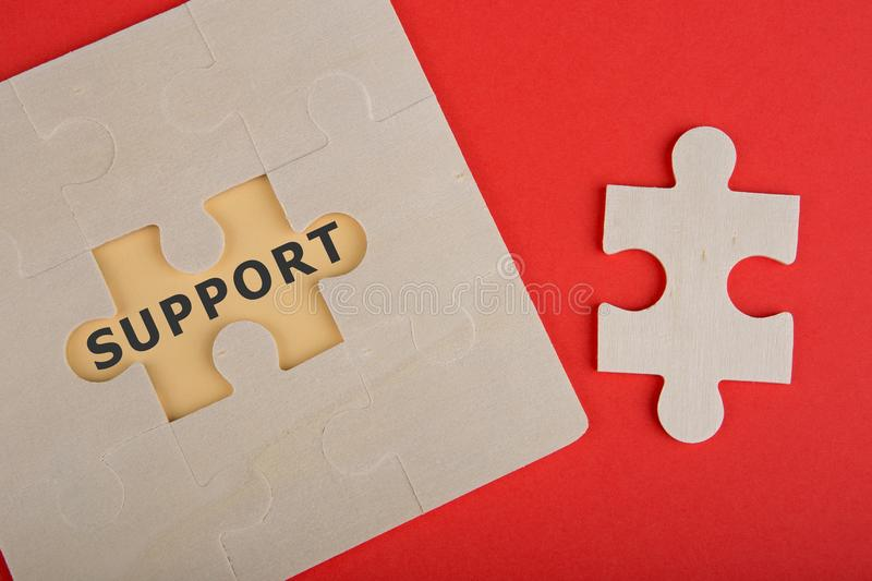 Jigsaw Puzzle Pieces with words & x22;Support& x22; on red background royalty free stock image