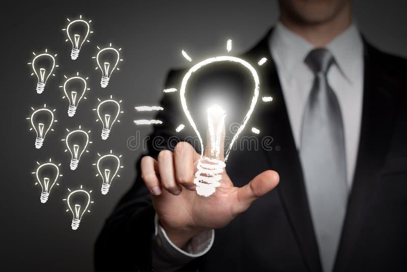 Business teamwork innovation concept - businessman presses virtual touchscreen interface button - glowing light bulb stock image
