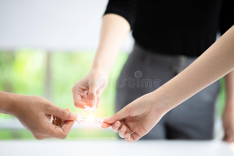 Business teamwork, partnership and brainstorm concept. Group of business people assembling jigsaw puzzle stock image
