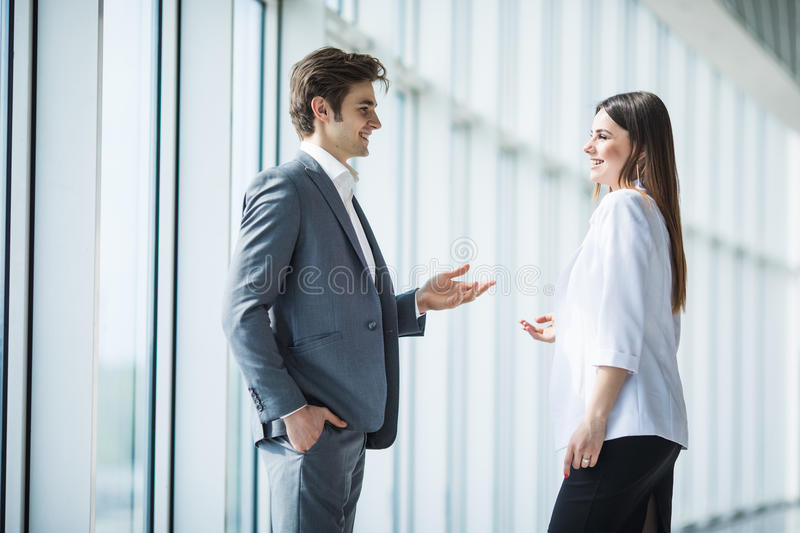 Business, teamwork, partnership, cooperation and people concept - business people talking each other over panoramic office windows. Business, teamwork stock images