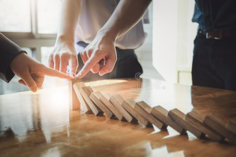 Business teamwork risk control concept, Business team protect wooden block fall to planning and strategy in risk to business royalty free stock photography