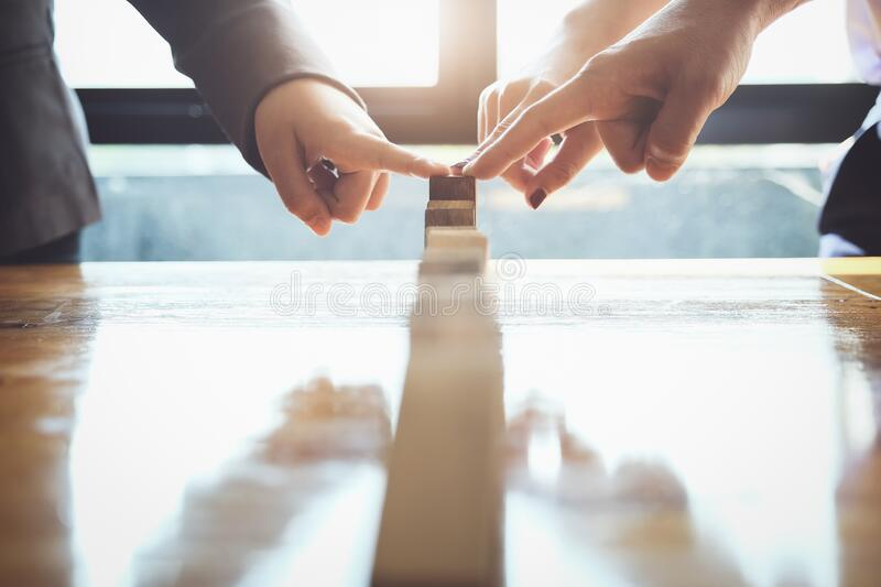 Business teamwork risk control concept, Business team protect wooden block fall to planning and strategy in risk to business stock photo
