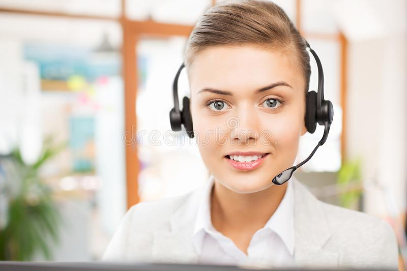 Helpline operator in headset working at office. Business, technology and communication concept - female helpline operator in headset working at office stock photography