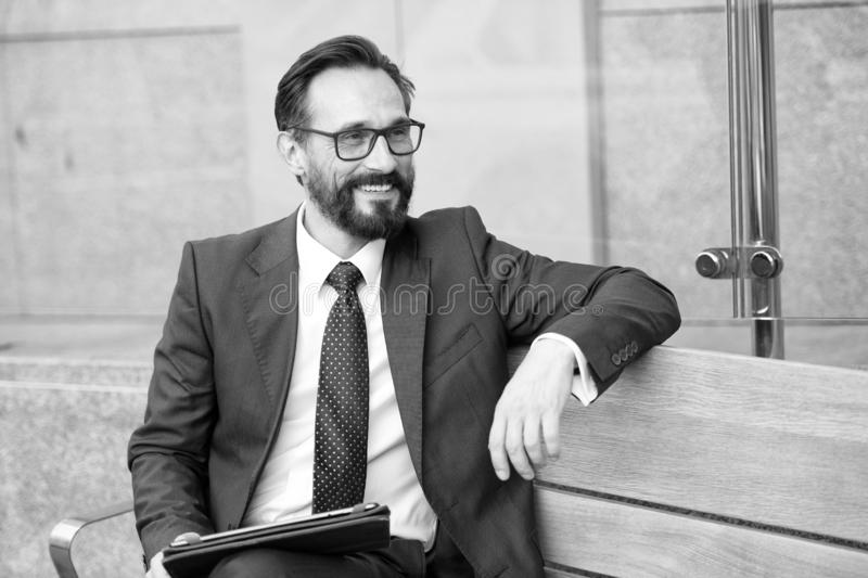 Business, technology, communication and people concept-man with tablet on city street bench. Portrait of handsome smiling man in s. Uit relaxing outdoors on royalty free stock images