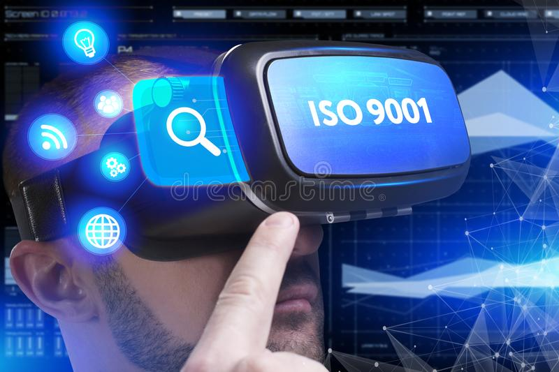 Business, Technology, Internet and network concept. Young businessman working in virtual reality glasses sees the inscription: IS. O 9001 stock photography