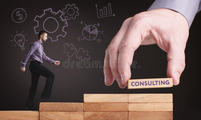 Business, Technology, Internet and network concept. Young businessman shows the word: Consulting stock photography