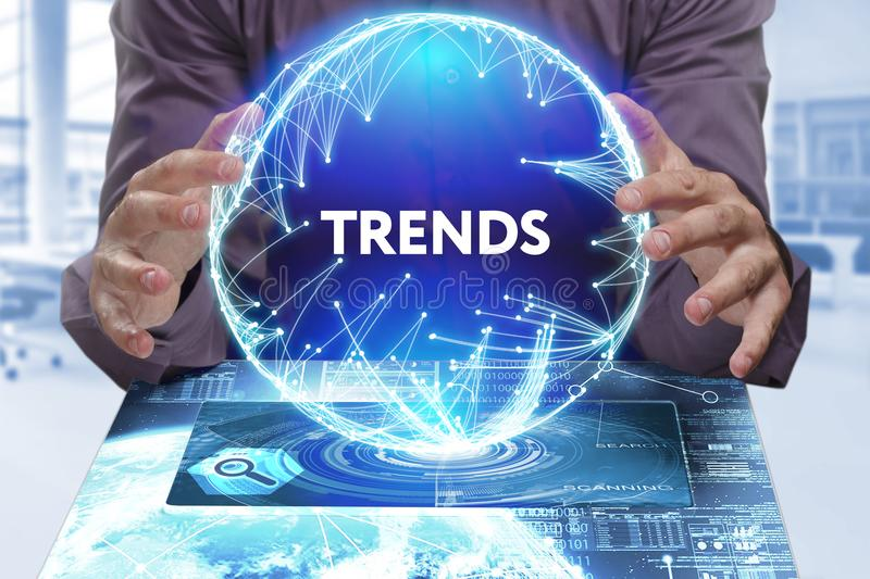 Business, Technology, Internet and network concept. Young businessman shows the word on the virtual display of the future: Trends stock image