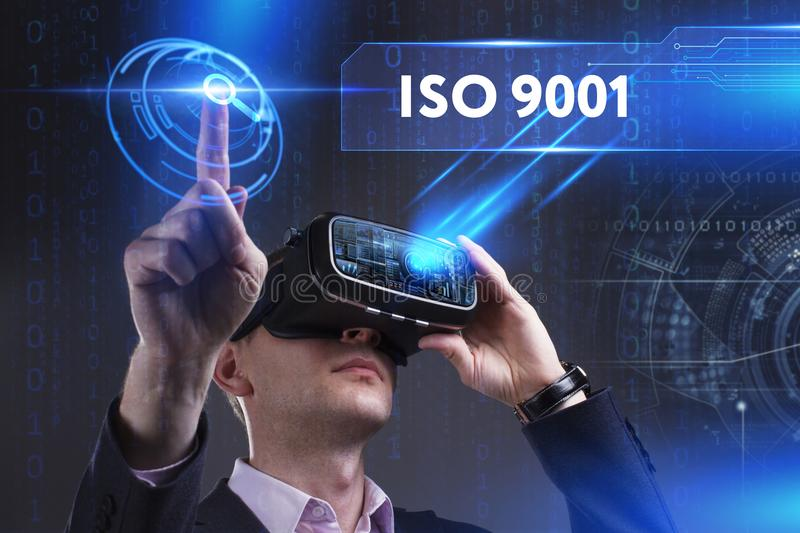 Business, Technology, Internet and network concept. Young busine. Ssman working in virtual reality glasses sees the inscription: ISO 9001 stock photos