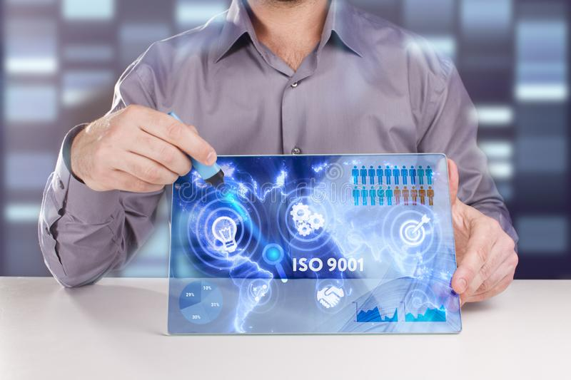 Business, Technology, Internet and network concept. Young businessman working on a virtual screen of the future and sees the. Inscription: ISO 9001 stock photo