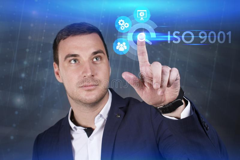 Business, Technology, Internet and network concept. Young businessman working on a virtual screen of the future and sees the. Inscription: ISO 9001 stock photography
