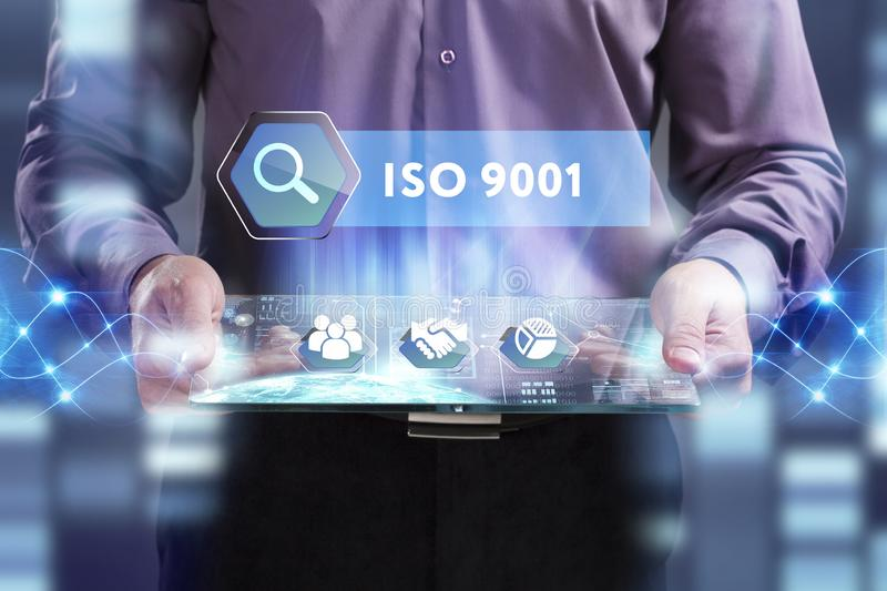 Business, Technology, Internet and network concept. Young businessman working on a virtual screen of the future and sees the. Inscription: ISO 9001 stock photos