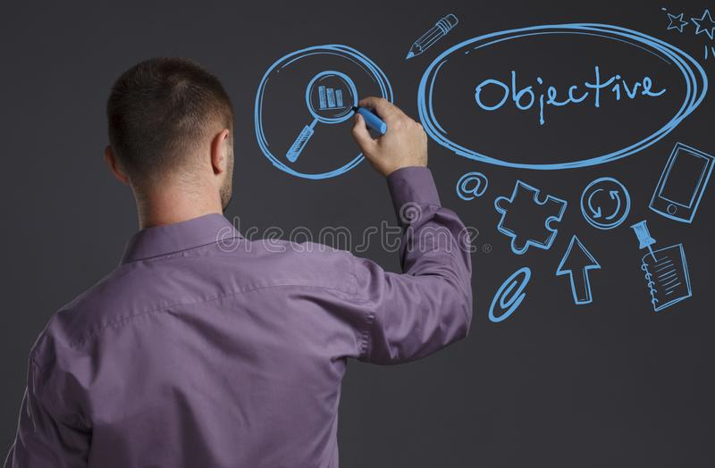 Business, Technology, Internet and network concept. A young businessman writes on the blackboard the word: Objective royalty free stock photography
