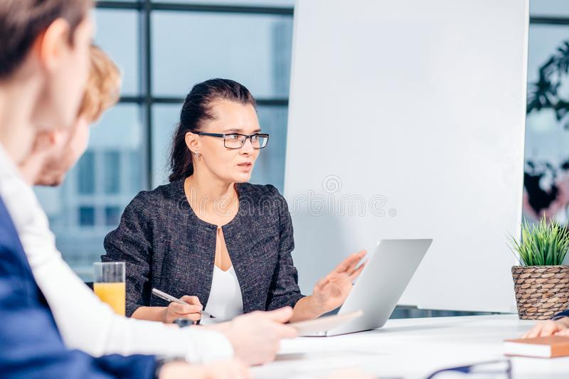 Business, technology and office concept - smiling female boss talking to team royalty free stock photo