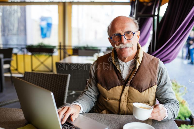 Senior man with laptop computer drinking coffee at city street cafe stock images