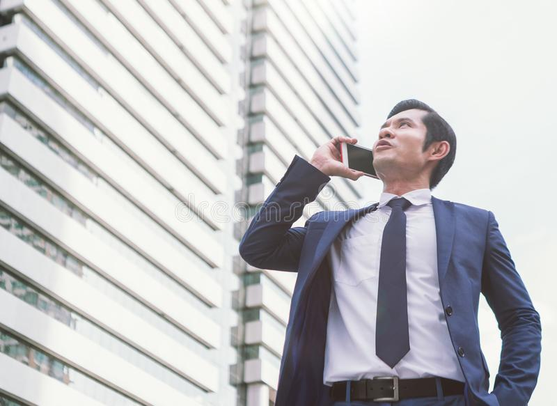 Business, technology and people concept - serious businessman with smartphone talking over office building stock image