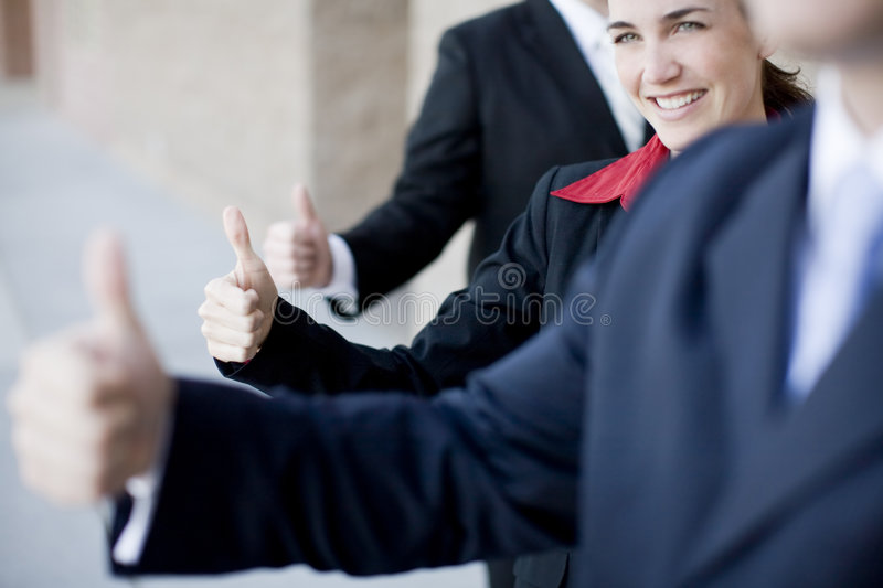 Business Thumbs-up. Three business people in suits giving thumbs up royalty free stock images