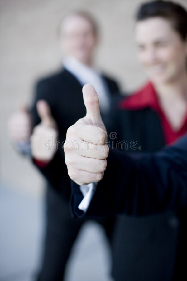 Business thumbs up. Three businesspeople in a row standing giving thumbs up royalty free stock photos