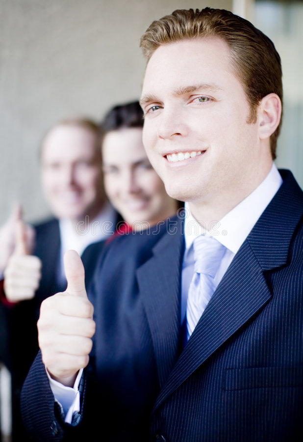 Business thumbs-up. Close view of three businesspeople in a line giving thumbs up royalty free stock image