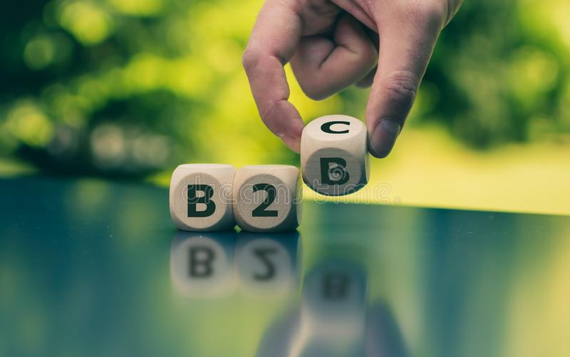 Business to Business or Busness to Consumer? Hand turns a dice and changes the expression stock photos
