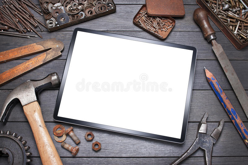 Business Tools Computer Tablet. A tablet computer surrounded by tools, nails and screws on a wood workbench royalty free stock photos