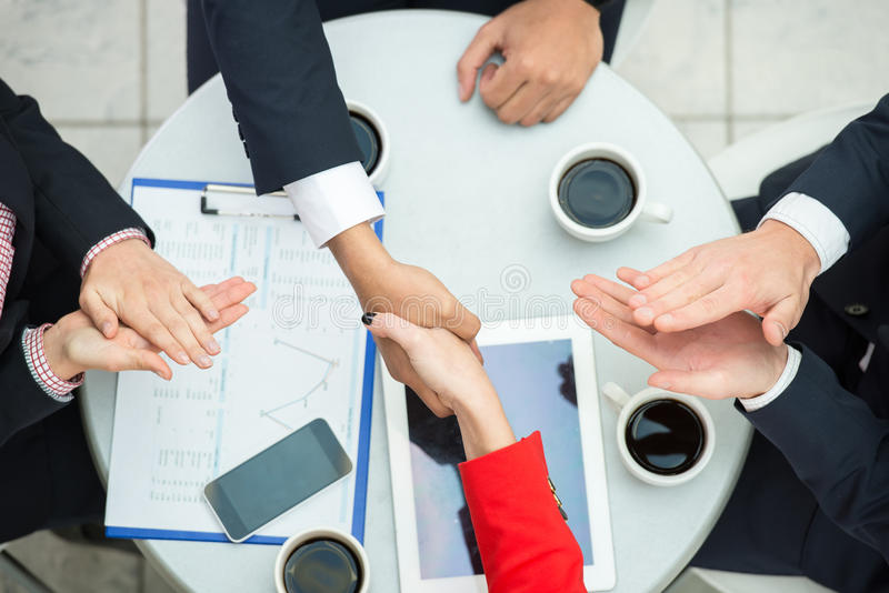 Business. Top view of business people are shaking hands, others clap their hands royalty free stock images