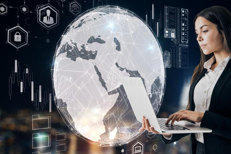 Business trading concept with trader woman with laptop behind digital earth globe background royalty free stock image