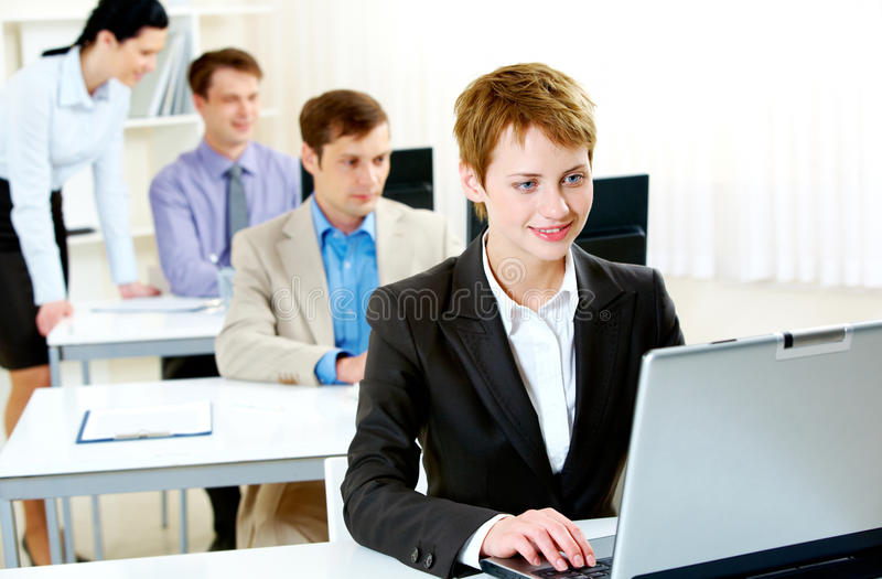 Business training. Portrait of business people typing on laptop during business training