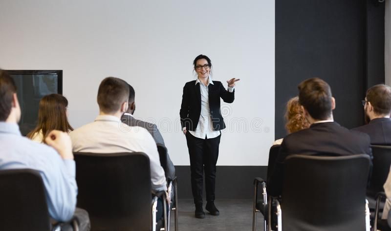 Business training. Female speaker giving lecture to audience royalty free stock images
