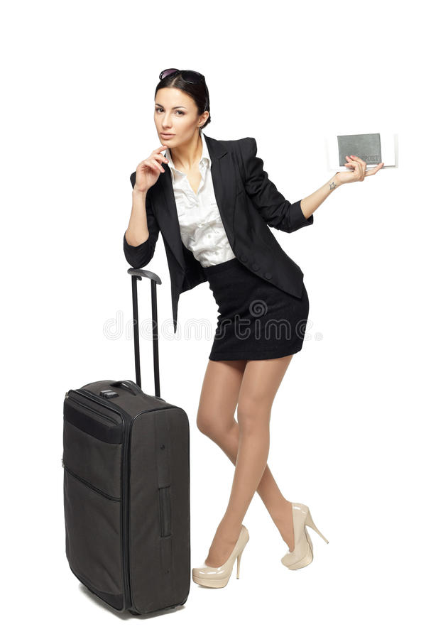Business travel. Full-body portrait of young business woman standing with black travel bag and holding the tickets with passport isolated on white background royalty free stock images