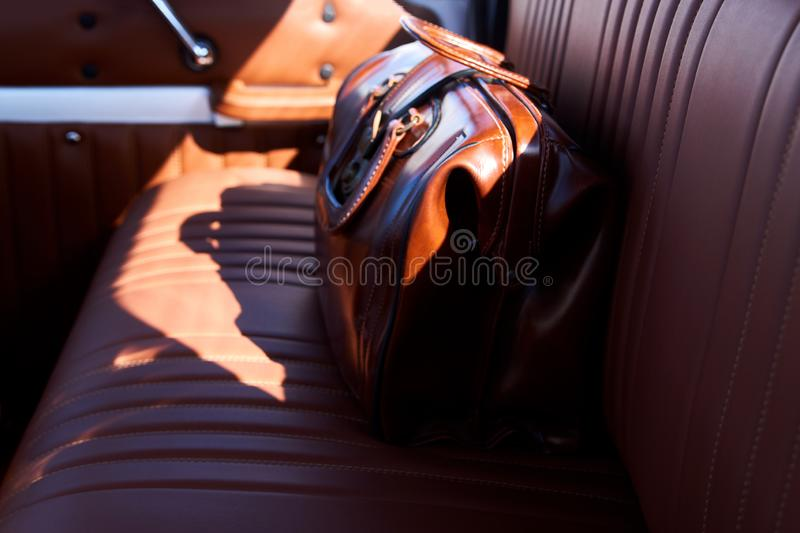 Business travel concept with brown leather bag on old car seat stock images