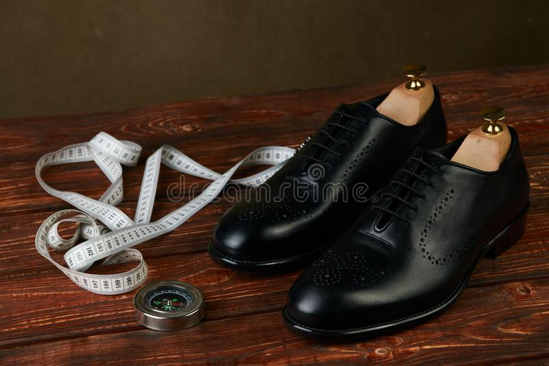 Business travel concept with pair of black mens shoes, compass and measuring tape stock photos