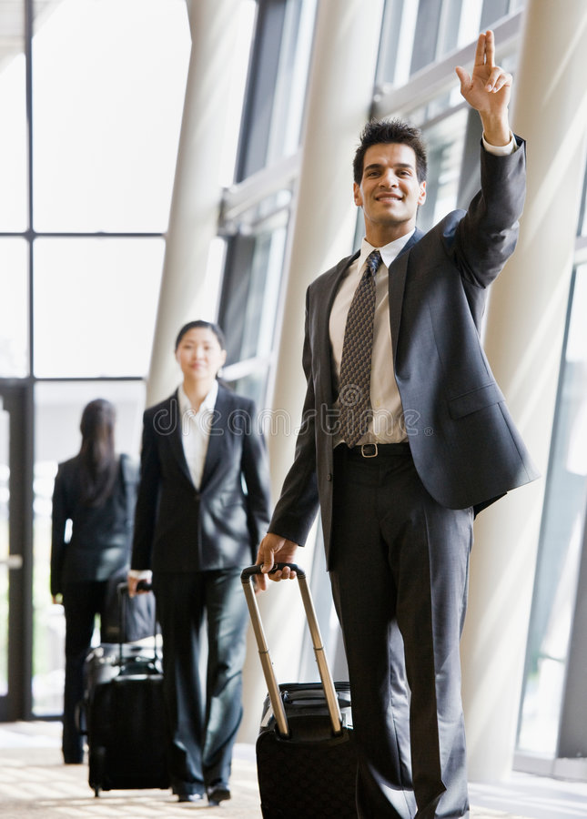 Business traveler pulling suitcase and gesturing stock photo