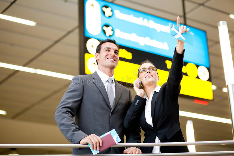 Business travellers at airport. Two business travellers checking boarding information at airport royalty free stock photography