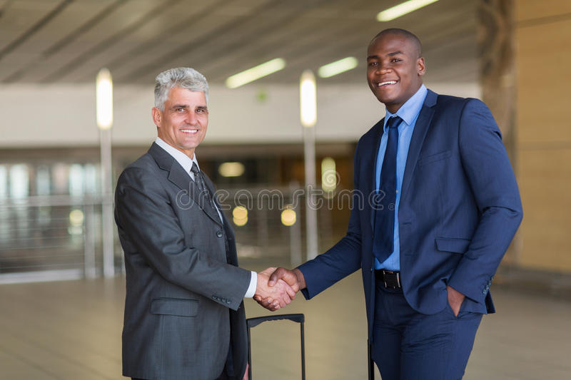 Business travellers greeting. Portrait of business travellers greeting at airport royalty free stock images