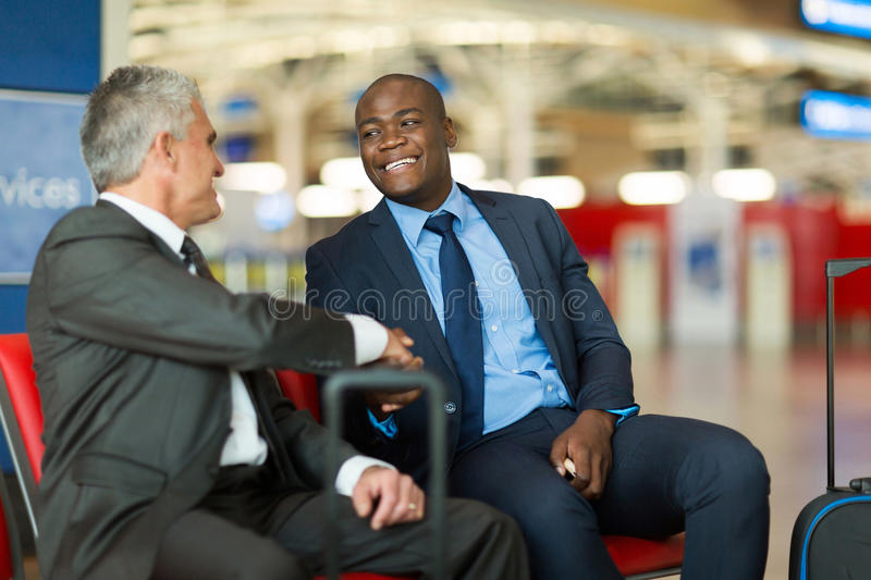 Business travellers handshaking. Friendly business travellers handshaking at airport royalty free stock photography