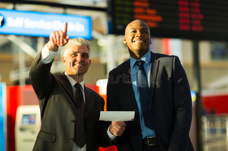 Business travellers pointing. Handsome business travellers pointing at flight information board royalty free stock photos