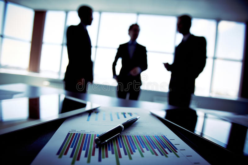 Business trio. Shadowy business trio holding a briefing concerning the reported statistic data stock photography