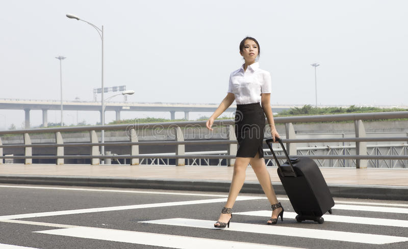 Business trip. An asian miss staff is in business trip and passing crosswalk royalty free stock image