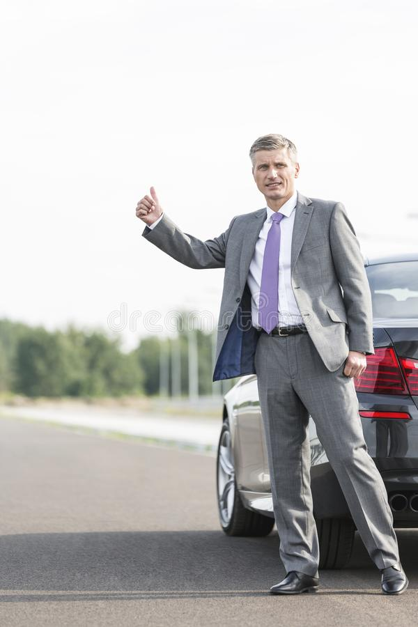 Businessman hitchhiking while standing by breakdown car on road royalty free stock photos