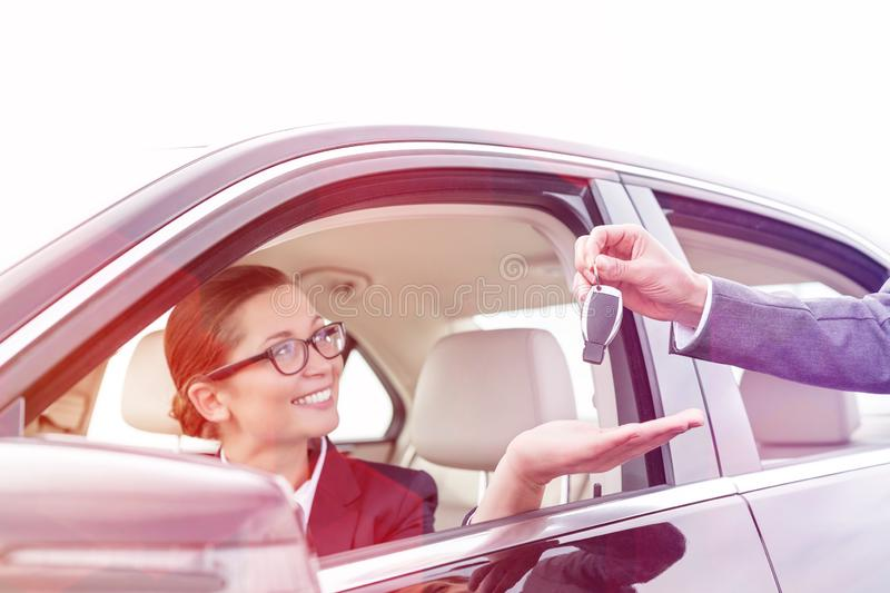 Cropped hand of woman giving car key to smiling businesswoman royalty free stock photos
