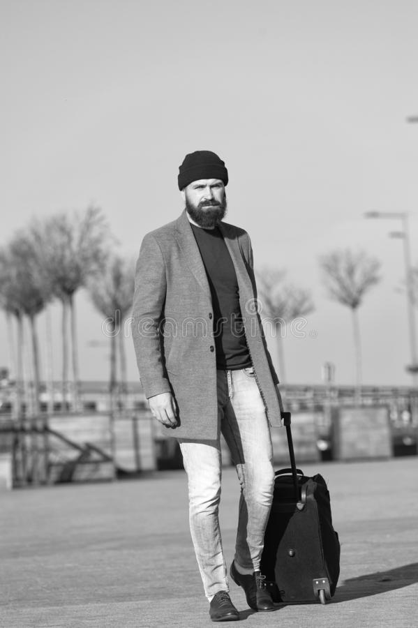 Business trip. Man bearded hipster travel with big luggage bag on wheels. Let travel begin. Traveler with suitcase. Waiting transportation to airport railway royalty free stock photography