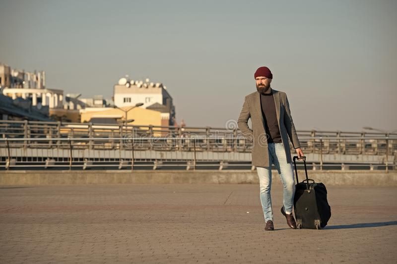 Business trip. Man bearded hipster travel with big luggage bag on wheels. Let travel begin. Traveler with suitcase. Arrive to airport railway station. Hipster stock photo