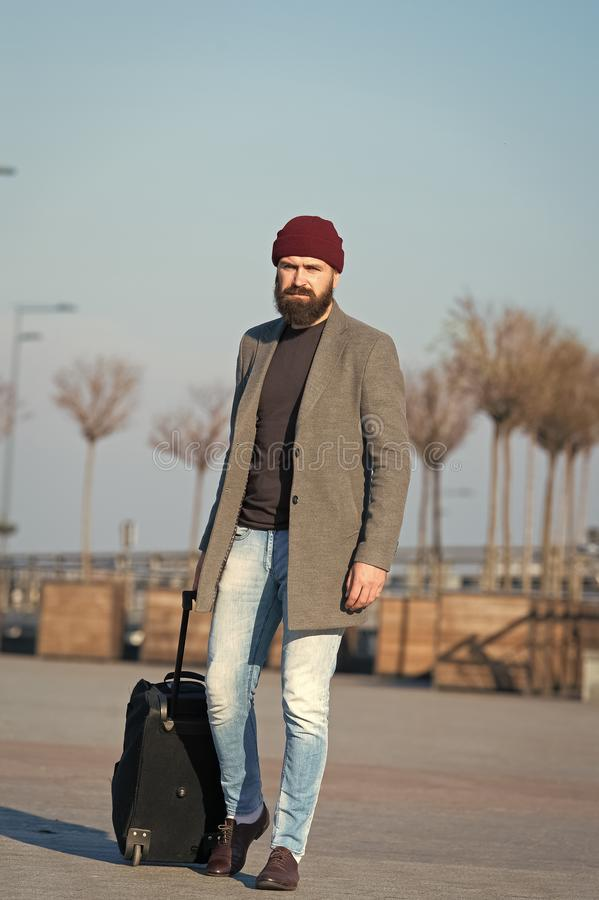 Business trip. Man bearded hipster travel with big luggage bag on wheels. Let travel begin. Traveler with suitcase. Waiting transportation to airport railway royalty free stock photos
