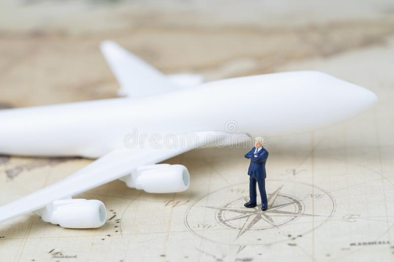 Business trip planning or travel concept, miniature adult businessman standing on with toy airplane on vintage world map with com stock photo