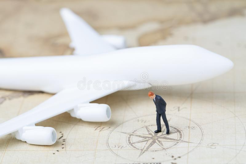 Business trip planning or travel concept, miniature adult businessman looking at compass on vintage world map with toy royalty free stock photo