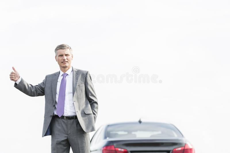 Business professional hitchhiking by breakdown car against sky stock photo
