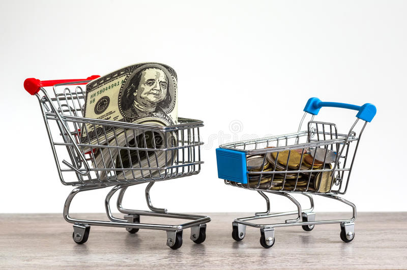 Business trolley with money. Basket full of coins, dollar bills on a white background, money, currency, business royalty free stock images